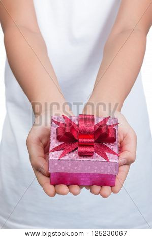 Two female hands holding and presenting a small and shiny pink box of present with shiny red bow on top against blurred white tshirt and white background