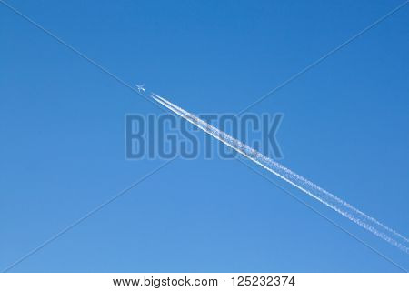 Wanderlust - Large passenger plane with contrails in the blue sky