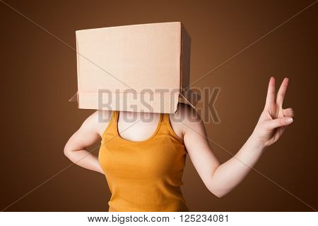 Young girl standing and gesturing with a cardboard box on his head