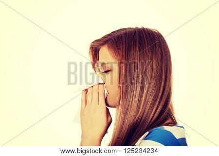 Teenage ill woman using a tissue