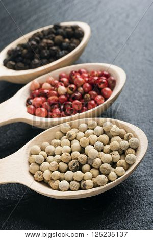 Peppercorns in wooden spoons on dark textured background.