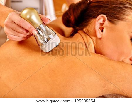 Woman receiving electroporation back therapy at beauty salon. Close-up.