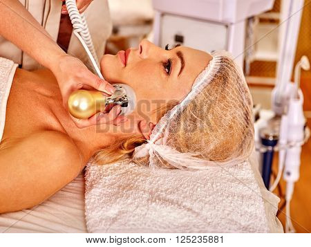 Close up of relaxed young woman receiving electroporation  facial therapy at beauty salon.