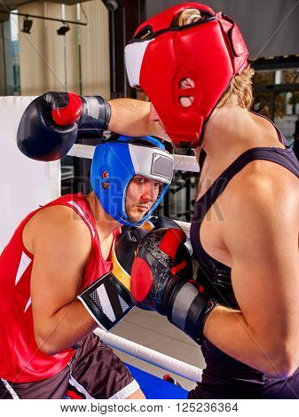 Two  men boxer wearing helmet and  gloves boxing . Fight boxing style. They are serious.