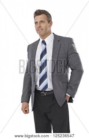 Portrait of elegant businessman looking away, hand in pocket.