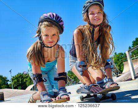 Two Children in helmet skateboarding on his skateboard outdoor. lower plan. Very happy.