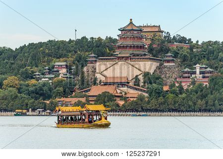 Beijing China - October 14 2013: A dragon boat traveling on the Kunming Lake Beijing China. Summer Palace in the center.