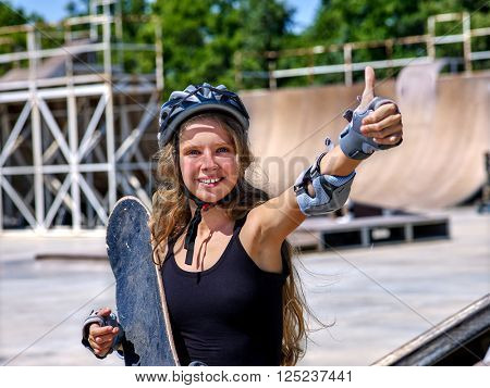 Girl holding  skate and roller skates in sport park. Teen girl holding a skateboard in hand and shows his thumb.