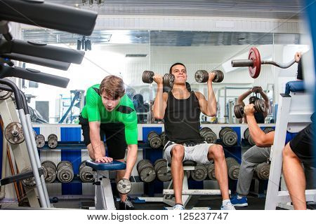 Group of men working on simulators, with dumbbells in the gym. They are serious.
