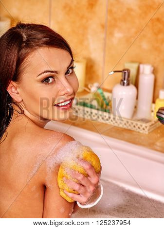 Young woman take bubble  bath. Woman washing her shoulder. She is happy.