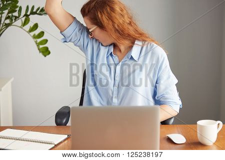Portrait Of A Young Woman Wearing Blue Shirt Disgusting With Bad Smell Of Her Wet Armpit While Worki