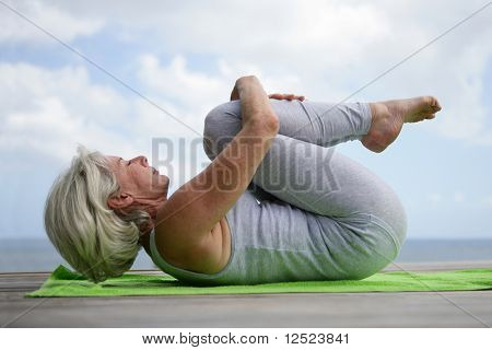 Senior woman exercising by the sea