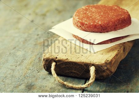 Raw Ground beef meat Burger steak cutlets on vintage wooden boards