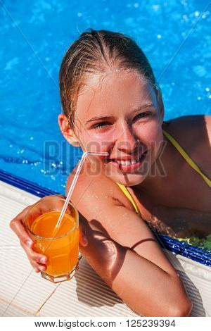 Child drinks a cocktail in the pool.