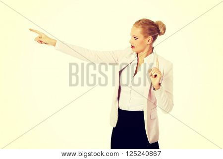 Young focus business woman explaining something and pointing at board or copyspace