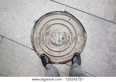 Male Feet Standing On Rusty Sewer Manhole