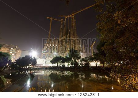Barcelona, Spain - November 11, 2015: Basilica church Sagrada Familia seen from Placa de Gaudi at night. The church is designed by architect Antoni Gaudi and is still under construction. It is a famous tourist attraction in Barcelona.