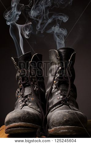Old used working boots with smoke on a dark background