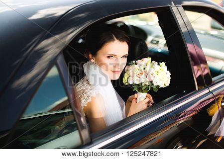 Close-up portrait of a pretty bride in a car window.