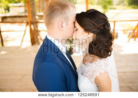Wedding couple. Beautiful bride and groom. Just married. Close up. Happy bride and groom on their wedding hugging. Groom and Bride in a park. wedding dress.