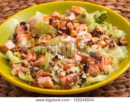 Iceberg salad with baked salmon flakes and crushed walnuts/pecans. Horizontal shot