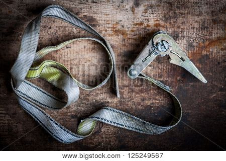 Color image of some ratchet tie down on a wooden plank.