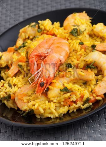 Seafood risotto with shrimps curry and herbs. Vertical shot