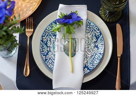 Wedding table setting with blue anemones and iris.