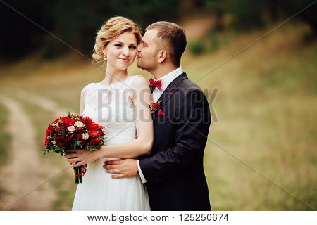 Happy wedding couple lovely hugging and smiling each other in autumn park. Gentle photo. Blonde bride with bouquet of red flowers.