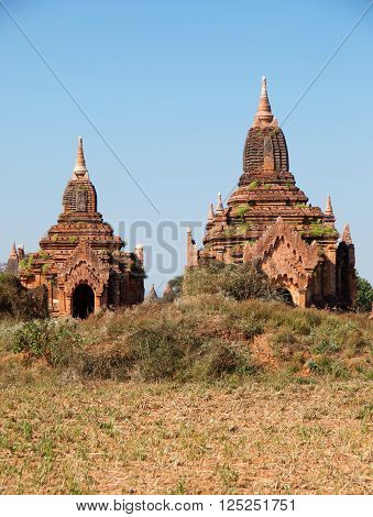 Two ancient pagodas in Bagan Myanmar blue sky in background