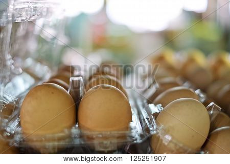 A lot of brown  fresh eggs, in box at a market