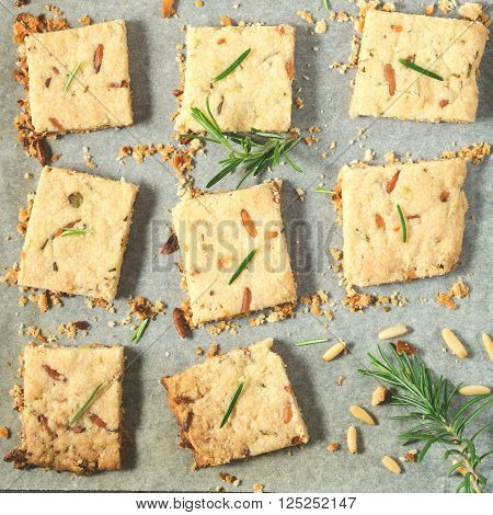 Butter cookies with rosemary, pignoli and pistachio nuts on baking parchment, decorated with rosemary sprigs