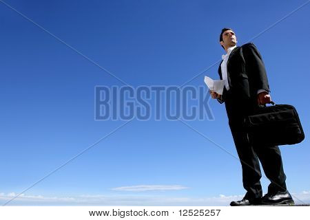 Businessman standing outside with blue sky