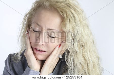 mature woman with a toothache over a white background