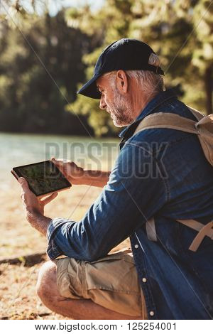 Close up portrait of senior man with backpack sitting by a lake and using digital tab in the forest for navigation.