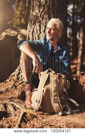 Portrait of senior man looking away while sitting by a tree. Senior man with a backpack outdoors on a summer day. ** Note: Shallow depth of field