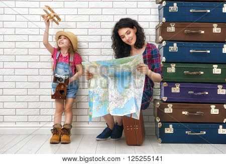 happy family preparing for the journey. mother and daughter looking at a map and choose a country to travel.