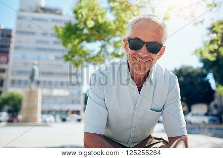 Happy Senior Man Sitting Outdoors In The City