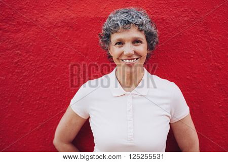 Portrait of senior woman standing against red background. Smiling mid adult female against red wall.