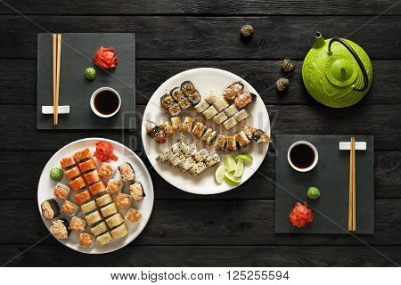 Japanese food restaurant, sushi maki gunkan roll plate or platter set. Set for two with chopsticks, ginger, soy, wasabi and teapot. Sushi at rustic wood background and black stone. Top view at black.