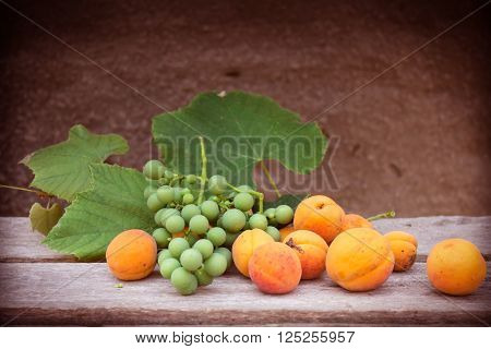 Apricots and grapes on a brown wooden table