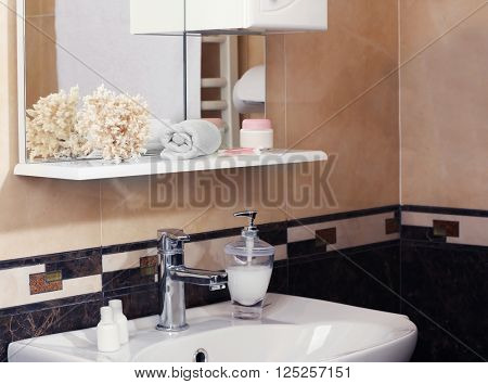 Bathroom interior with sink, shelf, towel and liquid soap
