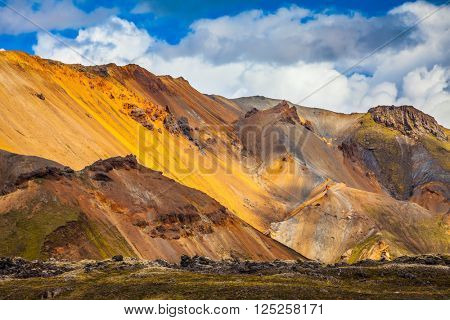Bright, multi-colored rhyolite mountains - yellow, orange, green and blue. Summer volcanic tundra.  Travel to Iceland in July