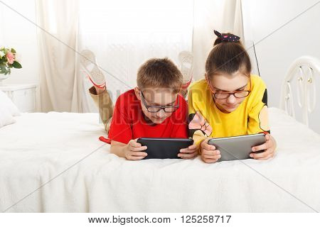 Two children, siblings on parents' bed at morning with laptop and tablet. Brother and sister play computer games. Siblings and gadgets. Children with pet, chiwawa dog in bed. Children in glasses.