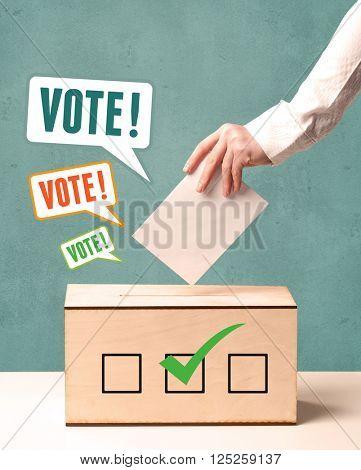 A hand placing a voting slip into a ballot box