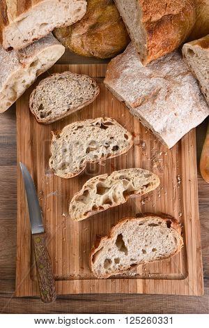 A variety of fresh baked loaves of bread, with slices on a wood cutting board. Top view in Vertical format.