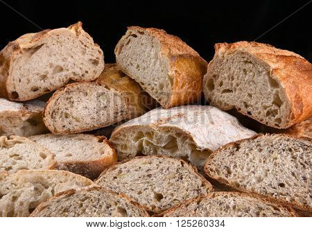 A variety of fresh baked loaves of bread, the loaves are cut in half and sliced.