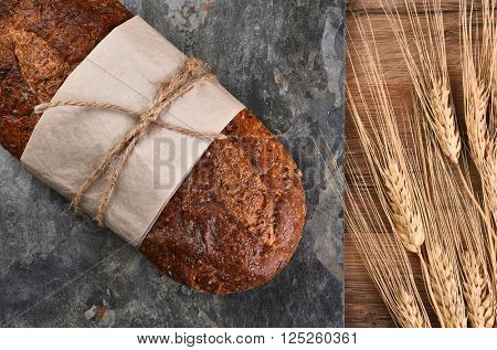 Top view of a loaf of multi-grain bread on a slate surface and wheat stalks.