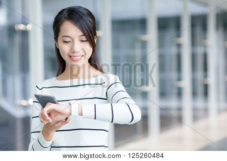 Woman using cellphone to connect with smart watch