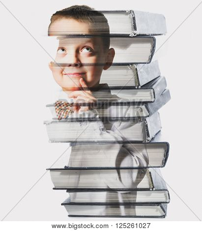 thinking school boy mixed with pile of books, against gray background